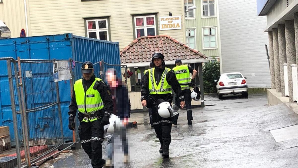 Her blir den mistenkte personen tatt med av politiet etter å ha kastet et lysrør under demonstrasjonen i Arendal sentrum.