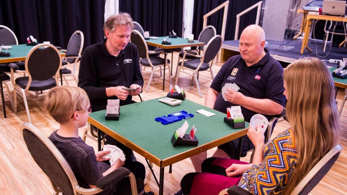 Reidun Margrethe Moe, sonen Markus Hansen Moe og Tormod Røren frå NM-komiteen lærer Lars Nibstad å spele bridge.