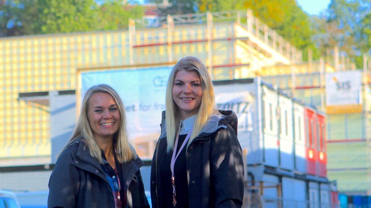 Elin Tuft (t.v.) og Iselin Johannesen gler seg stort på vegner av ungdomen som om nokre månader kan ta flett nye Ung Arena i bruk. Bak dei reiser bygget seg i stort fart.