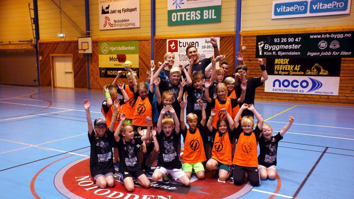 Heidi Løke og Joakim Hykkerud sammen med flere av de unge deltakerne på håndballskolen