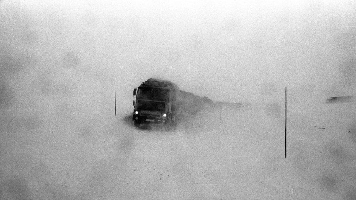 Eit vogntog sneglar seg fram gjennom snøføyka. Rv7 over Hardangervidda.