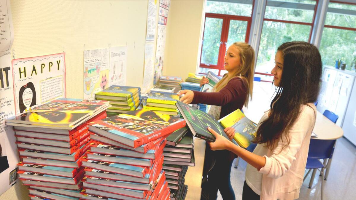 Streikende lærere i Arendal mener utdeling av bøker kan være streikebryteri. Her får Thea Gustad Naustvoll og Mia Haakstad sine bøker på Hisøy skole.