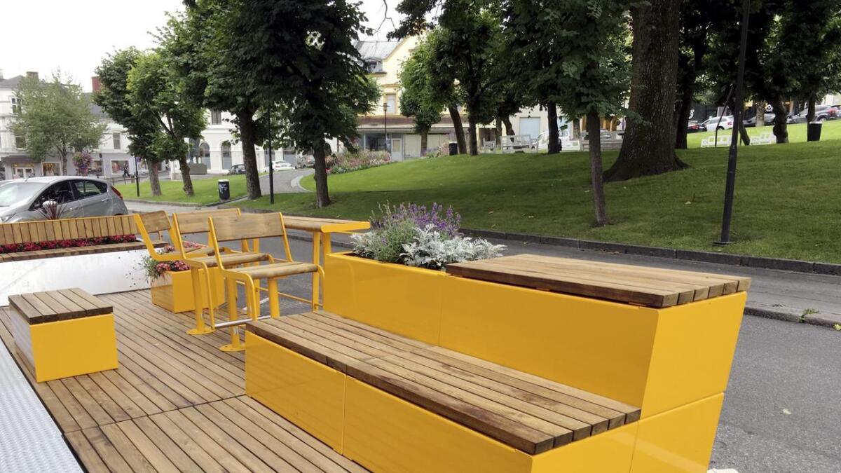 Utplassering av gule benker som tar parkeringsplasser i et område der det står mange tomme benker i parken i bakgrunnen skaper avmakt, mener artikkelforfatteren.